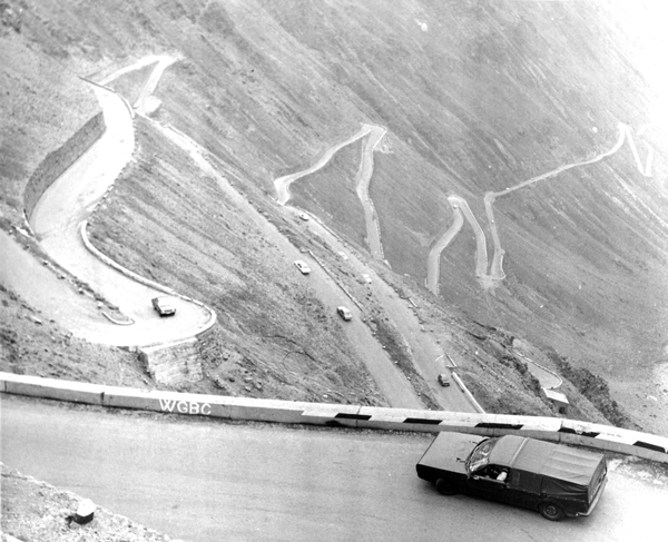 aerial view of camouflaged car on mountain hair-pin bend