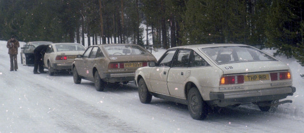 four cars parked in line on snow-covered roadblack camouflaged car with yellow tape simulating a grille
