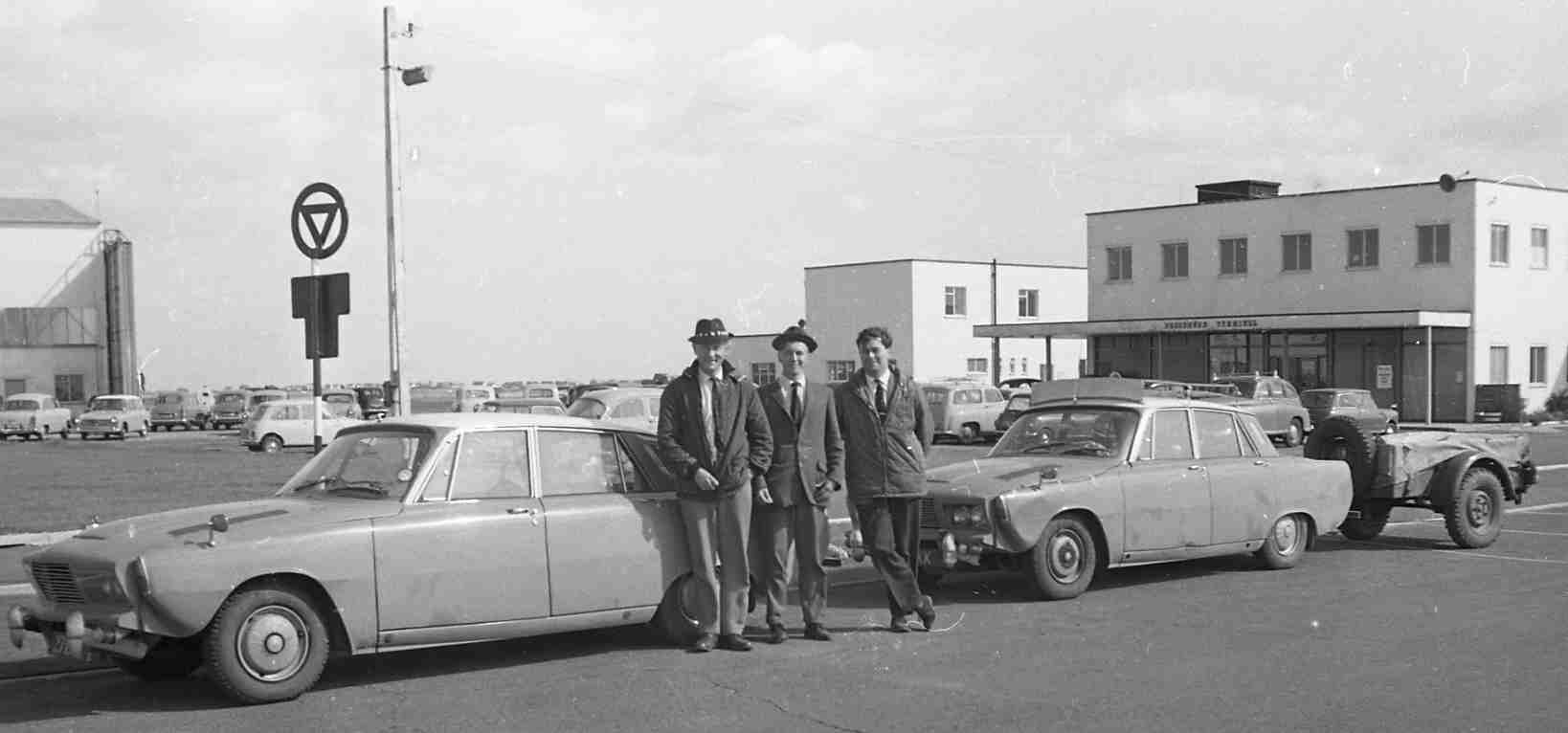 two parked cars, one with trailer. three men standing between them