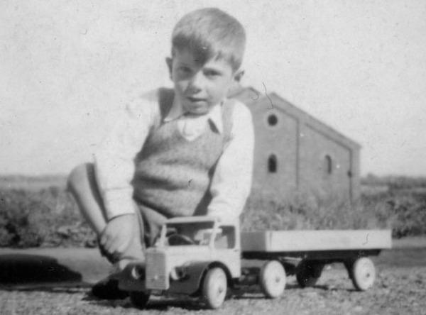 boy sitting next to model of articulated lorry